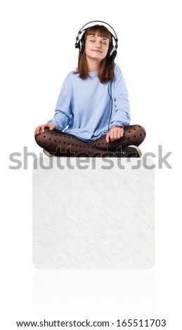 young woman listening to music sitting on a white box on white