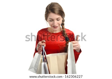 Young woman looking inside the shopping bags.Girl happy about the gift. Isolated on white.