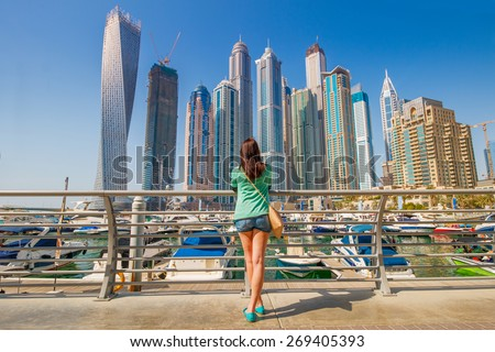 Young woman looking on skyscrapers in Dubai Marina