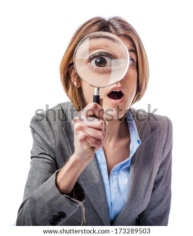 young woman looking through a magnifying glass isolated on white