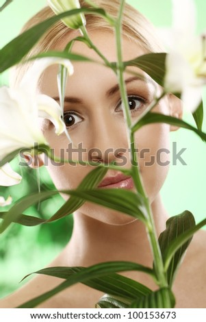 Young woman looking through green leaves of lily flower