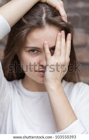 Young woman looking through their fingers against a brick wall