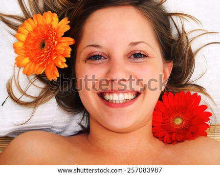 Young woman lying on white background with flowers in her hair waiting in spa studio for massage