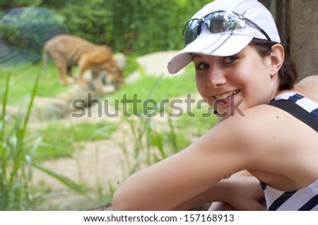 young woman near tiger in zoo