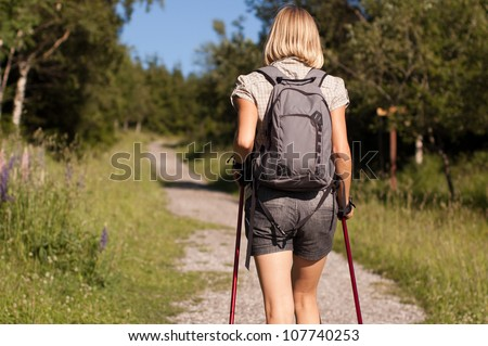 Young woman nordic walking in mountains