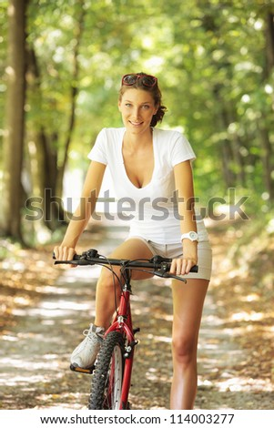 Young woman on a bicycle in the forest