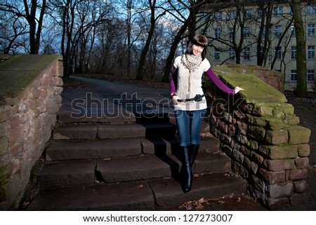 Young woman on a stair in park at twilight