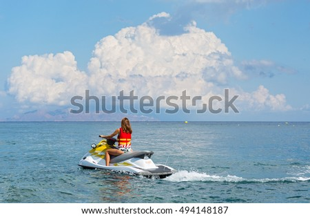Young woman on a water scooter rides on the sea
