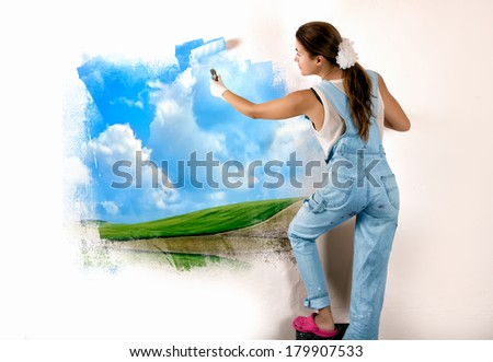 Young woman painting a nature landscape on wall with roller. Mural painting on wall. Ecologist