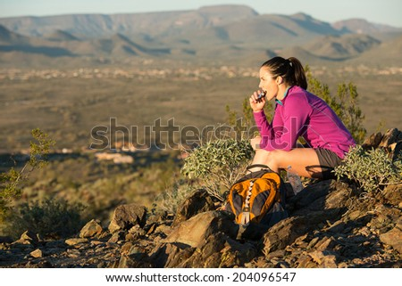 Young woman pauses at the top of a trail midway through her hike at Phoenix Sonoran Preserve in Phoenix, Arizona. She is having a snack.