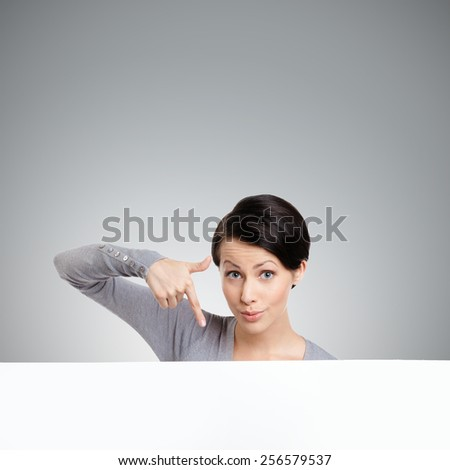 Young woman points down with finger , isolated on grey