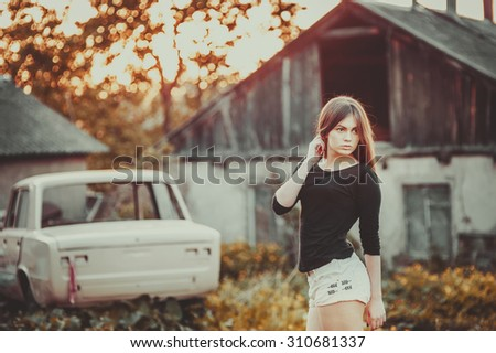 Young woman portrait against old building in sunset light.