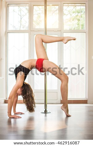 Young woman practicing a pose in a pole fitness class.