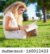 young woman reading a book at park on sunny day - stock photo