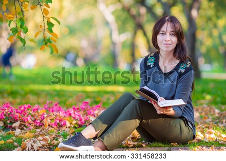 Young woman reading a book in beautiful autumn park