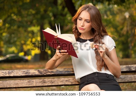 Young woman reading a book in park