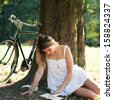 Young woman reading a book under a tree with bicycle in a park.  - stock
