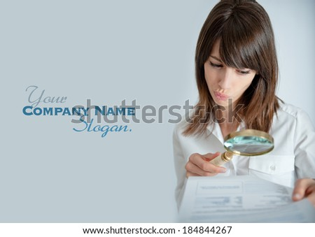 Young woman reading a document through a magnifying glass with a shocked expression