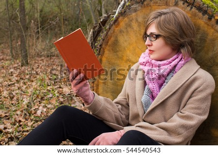 young woman reading book in the autumn forest
