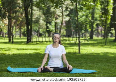 Young woman relaxing in a semi-lotus position with closed eyes on a green mat outdoor in a park.