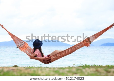 Young woman relaxing in the hammock on tropical beach