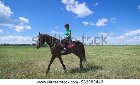 Young woman riding a horse on the green field. Walking enjoying the view. Impulsive