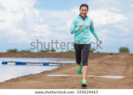 young woman running on trail with blue sky background