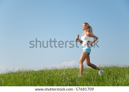 young woman running with dumbbells