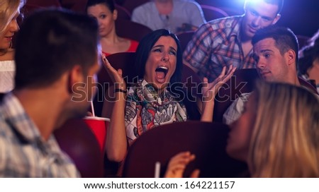 Young woman screaming with horror in movie theater, others watching.