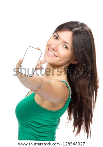 Young woman show display of mobile cell phone with white screen and smiling on a white background. Focus on hand with mobile phone