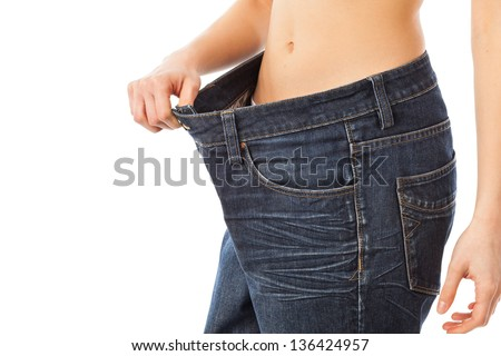 Young woman showing how much weight she lost, isolated on white