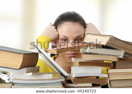 Young woman sitting behind books