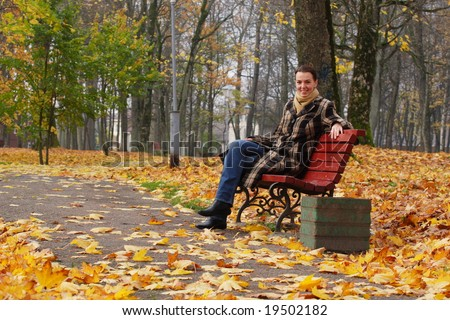 Young woman sitting on a bench in an autumn park