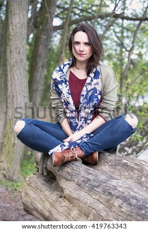 young woman sitting on a tree and smiles into camera