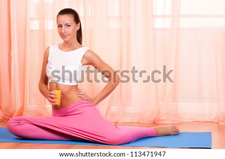 Young woman sitting on a yoga mat and holding glass of orange juice