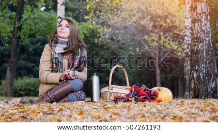 Young woman sitting on picnic drinking hot tea from a thermos in autumn park. Girl   the rug near the pumpkin Halloween theme