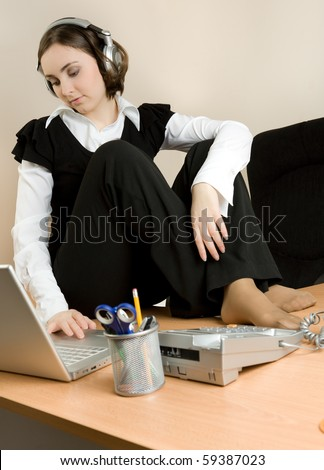 Young woman sitting on the desk and listening music