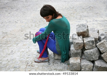 Young woman sitting on the stone brick