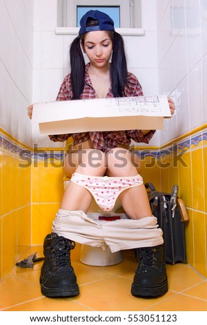 Young woman sitting on the toilet is studying construction plan. Female repairman resting on the toilet bowl.