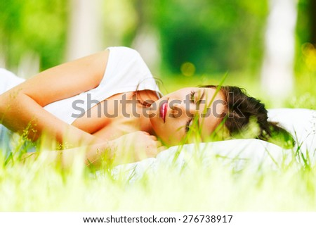 Young woman sleeping on white pillow in fresh spring grass