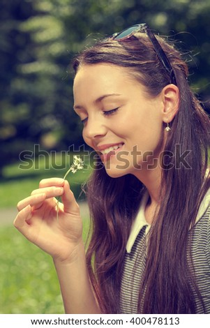 Young woman smells a flower on sunny day, intentionally toned.
