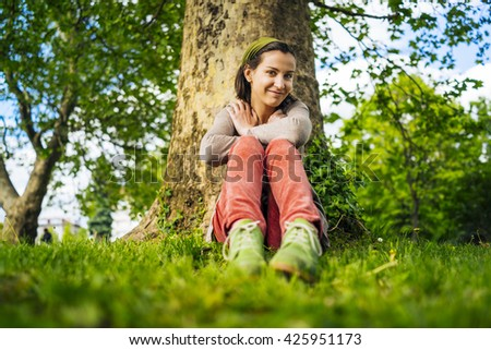 Young woman smiles to the camera seated under the tree at the park