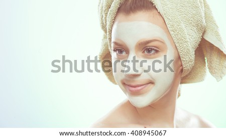 young woman smiling and looks not at the camera, she has a green towel and facial mask