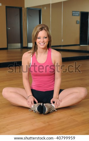 Young woman smiling and stretching on wood floor