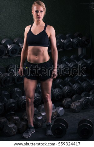 Young woman standing by a stack of free weights at a gym