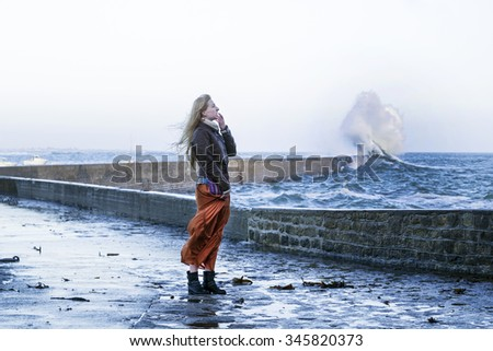 Young woman standing near the big wave on the pier in France, autumn winter storm