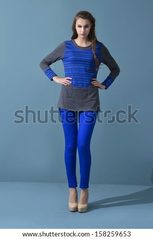 Young woman standing posing against on blue background
