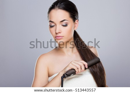 Young woman straightening her ponytail with hair straightener. Looking aside and down. Studio, indoors, waist up, grey background