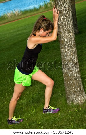 Young woman stretching her calf muscle, against a tree in a city park.