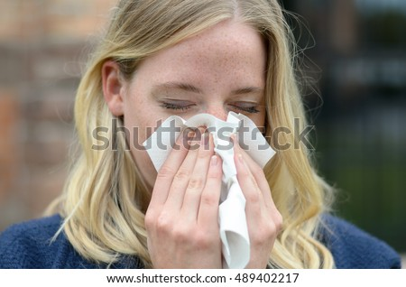 Young woman suffering from a seasonal cold and flu blowing her nose on a handkerchief as she stands outdoors in town in a healthcare and medical concept